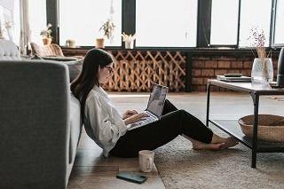 En kvinde sidder på gulvet i sin flot indrettede stue med sin computer i skøddet.